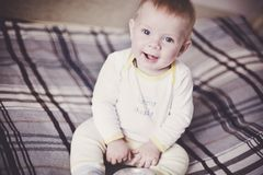 A cute blond baby in light clothes sits on a plaid bedspread on the bed and smiles. stock photo