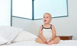 Cute blond baby sitting on bed alone Royalty Free Stock Images