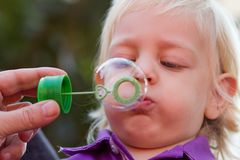 Cute blond boy blowing bubbles Royalty Free Stock Images