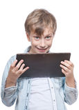 Cute blond boy in a blue shirt holding a tablet pc Royalty Free Stock Photography