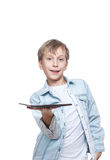 Cute blond boy in a blue shirt holding a tablet pc Royalty Free Stock Image