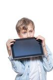 Cute blond boy in a blue shirt holding a tablet pc looking angry Royalty Free Stock Photos