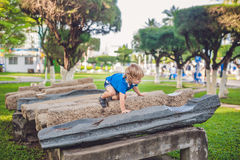 Cute blond boy climbs up the stone blocks on the playground. Childhood, concept Stock Images