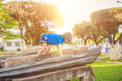 Cute blond boy climbs up the stone blocks on the playground. Childhood, concept Royalty Free Stock Photo