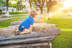 Cute blond boy climbs up the stone blocks on the playground. Childhood, concept Royalty Free Stock Photos