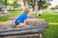 Cute blond boy climbs up the stone blocks on the playground. Childhood, concept Royalty Free Stock Images