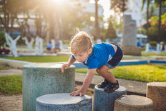 Cute blond boy climbs up the stone blocks on the playground. Childhood, concept Stock Photos
