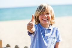 Cute blond boy doing thumbs up at beach. Stock Photos