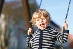 Adorable toddler boy having fun chain swing on outdoor playgroun stock image