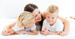 Cute blond boy with his sister and his mother. Lying on a bed Stock Photography