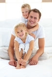Cute blond boy hugging his dad sitting on a bed royalty free stock photography