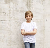 Cute blond boy in jeans and a white shirt stock photo