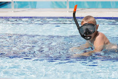 A cute blond boy learning to swim royalty free stock images