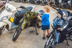 Cute blond boy looking at vintage motorcycle eatables new motorbike.  stock photo