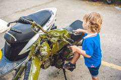 Cute blond boy looking at vintage motorcycle eatables new motorbike.  royalty free stock image