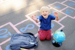 Cute blond boy playing hopscotch game after school with bags laying near Stock Images