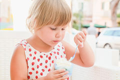 Cute blond Caucasian baby girl eats ice cream Royalty Free Stock Images