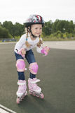 Cute blond caucasian girl skating on a track Stock Images