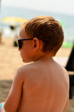 Cute blond child at the beach. Cute blond little   sad boy  sitting at the beach Royalty Free Stock Photo