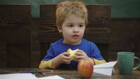 Cute blond child boy sitting in wooden chair and eating big red apple fruit. Portrait on blurred background, closeup.  stock video footage