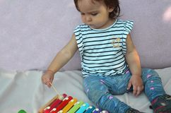 Cute child baby girl toddler playing with xylophone at home. Creativity and education concept. early stert for music royalty free stock photo