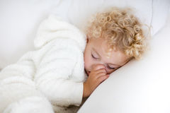 Cute blond curly little boy sleeping on white couch stock images