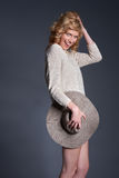 Cute blond fashion model in stretchy knitwear top and hat posing Royalty Free Stock Photos