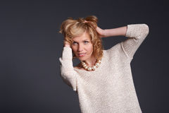 Cute blond fashion model in stretchy knitwear top posing - gray Royalty Free Stock Image