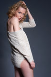 Cute blond fashion model in stretchy knitwear top posing - gray Stock Photos
