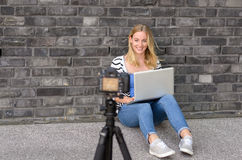 Cute blond female blogger with laptop recording video. While sitting and talking with gesturing hands for theme about video blogging Stock Image