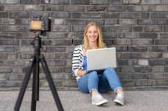 Cute blond female blogger with laptop recording video. While sitting and talking with gesturing hands for theme about video blogging Stock Photo