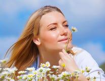 Cute female enjoying daisy smell Stock Image