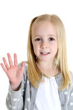 Cute blond girl with brown eyes with her hand up Stock Images