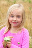 Cute blond girl in the grass. A cute little 6 year old girl with blond hair in tall grass wearing pink shirt. Shallow depth of field Stock Photography