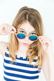 Cute blond girl with green sunglasses. Cute blond girl eleven years old standing near white wall with green sunglasses stock image
