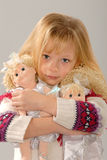 Cute blond girl with her dolls Stock Images