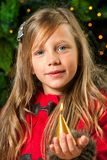 Cute blond girl holding golden candle. Cute blond girl holding golden candle at Christmas tree Royalty Free Stock Photos