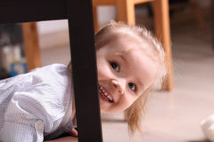 Cute blond girl laughing peeking out from behind table le Stock Images
