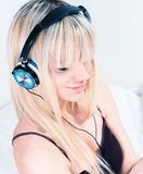 Cute blond girl listening to music on her smartphone Stock Photos