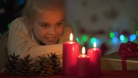 Cute blond girl looking at burning candles on Christmas eve, waiting for magic. Stock footage stock video