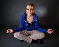 Cute blond girl in a meditation position Stock Photography
