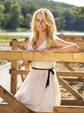 Cute blond girl near a horse stable Stock Photos