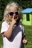 Cute blond girl picking her nose. Cute smiling blond child with sunglasses in purple with Little hearts, toddler having her finger in her nose, pick nose, bit of Royalty Free Stock Images