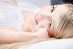 Cute blond girl on pillow. In bedroom Royalty Free Stock Image