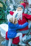 Cute blond girl with pink hoop in her hair  and  blue coat near Santa Claus Royalty Free Stock Photo