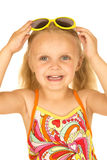 Cute blond girl playing with yellow sunglasses wearing swimsuit Royalty Free Stock Photography