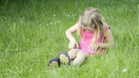 Cute blond girl in preschool age sitting in green grass playing with smart phone stock video footage