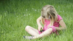 Cute blond girl in preschool age sitting in green grass playing with smart phone stock video