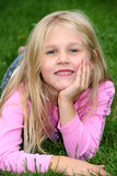 Cute blond girl relaxing in the grass Royalty Free Stock Image