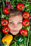 Cute blond girl shot in studio with vegetables aroound the head Royalty Free Stock Images